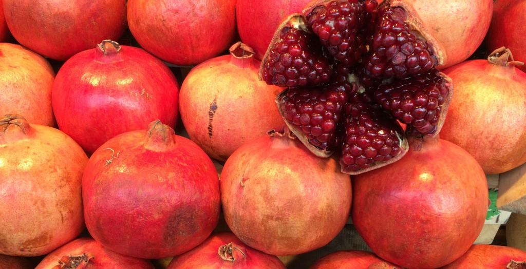 Haufen Granatäpfel ein Granatapfel aufgeschnitten